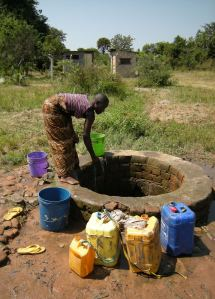 A girl called Happiness draws water from the one free well in Ulyankulu, Tanzania. Photo by Barbara Borst